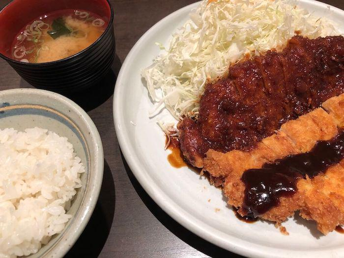 Nagoya-style red miso dish, a miso katsu set meal with a crispy golden brown cut of deep-fried pork drizzled in miso glaze, served with cabbage, rice, and miso soup