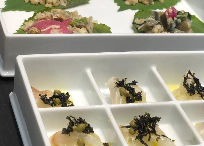 Small fish and noodle dishes served in white porcelain platers