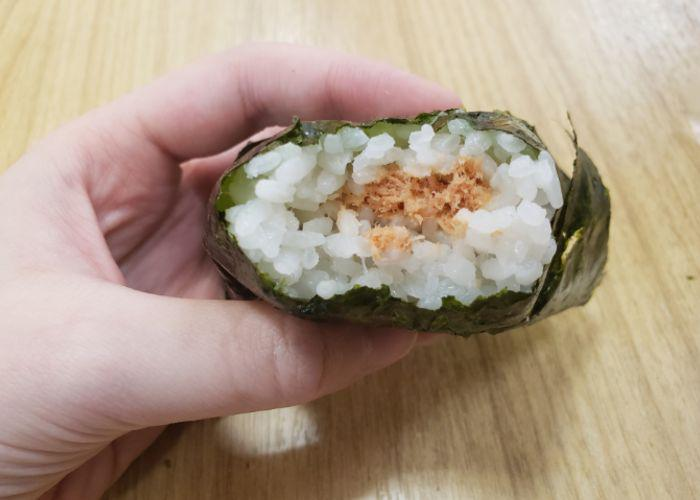 Hand holds out an onigiri with a bite taken out of it, revealing the center of grilled salmon