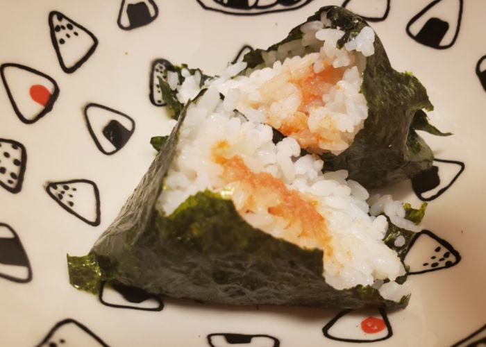 Mentaiko seasoned cod roe onigiri on a backdrop of a plate with onigiri illustrations