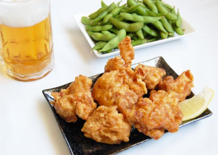 Japanese fried chicken, karaage, on a plate with a slice of lemon and a plate of edamame in the background