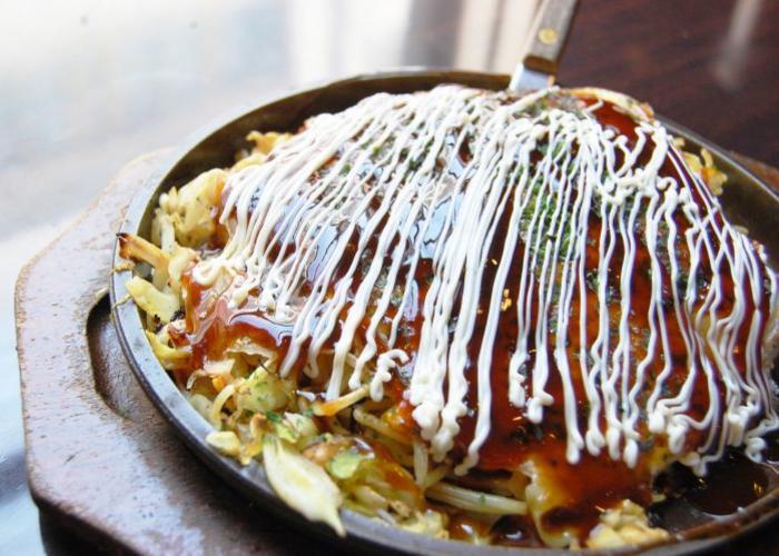Okonomiyaki, a savory Japanese pancake slathered in sauce and Japanese mayo