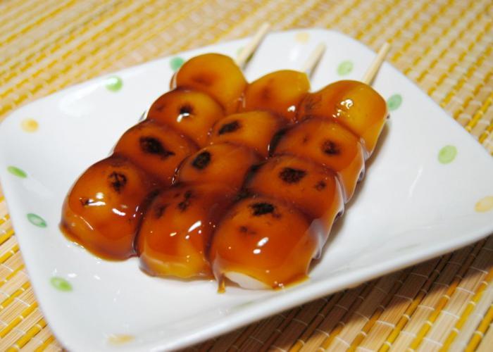 Skewers of mitarashi dango, glazed with a sweet sauce, on a plate