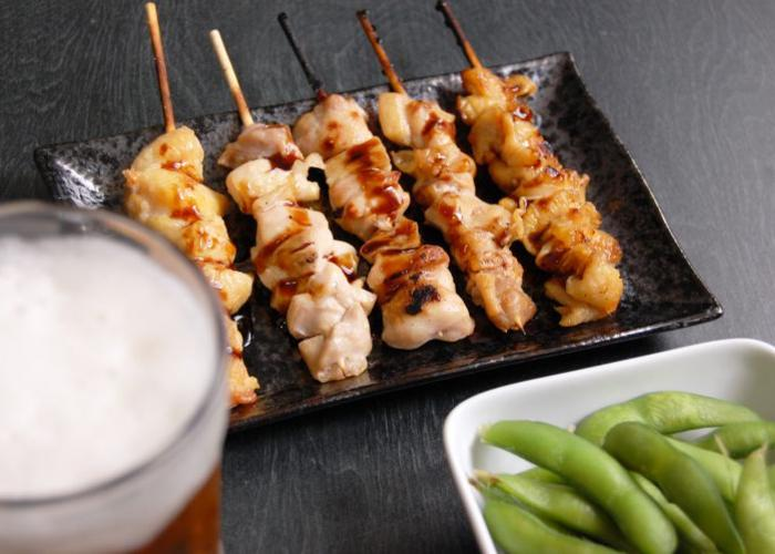 Yakitori grilled chicken skewers lined up on a plate