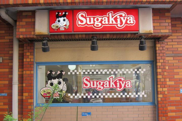 Sugakiya logo, red checkered with little girl holding ice cream and ramen