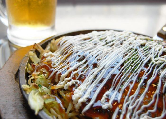 Okinomiyaki topped with sauce, on a griddle pan.