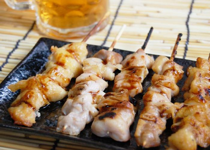 A plate of five yakitori grilled chicken skewers.