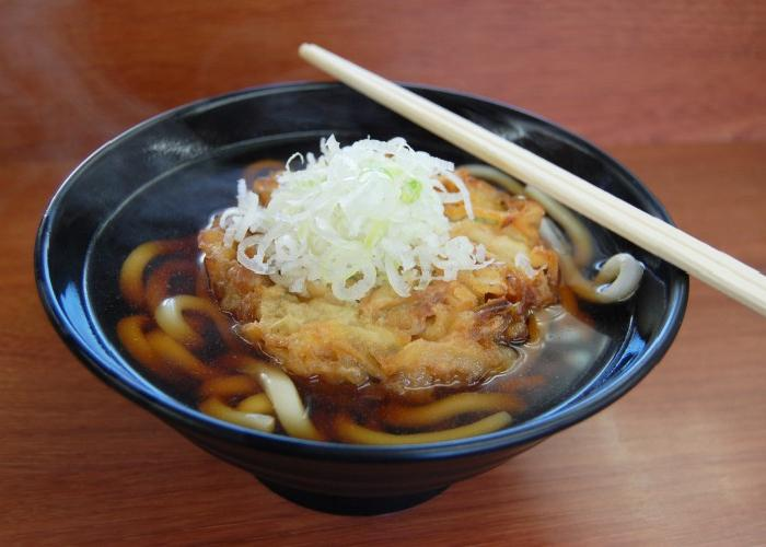 A bowl of udon noodles in thin soy broth, topped with vegetable tempura and chopped spring onions.