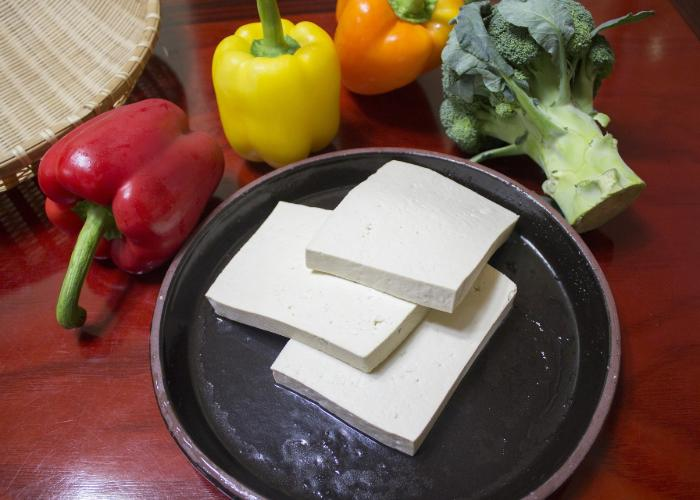A plate with three square slices of tofu, with bell peppers behind.