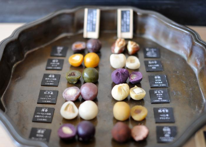 A platter with twelve varieties of colorful mochi sweets, with nuts and other fillings.