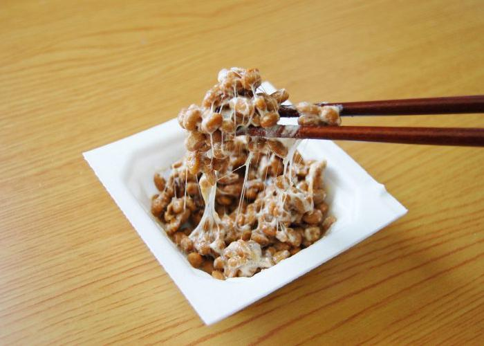 A square bowl with a sticky and stringy mass of natto, being picked up with chopsticks.