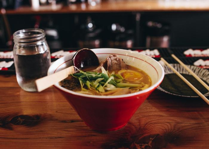 A bowl of miso ramen on a countertop, with a wooden ladle spoon resting atop.