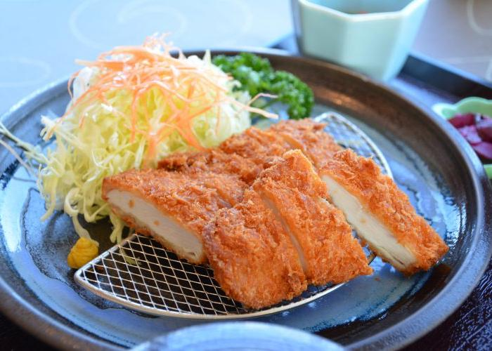 A katsu cutlet resting on a steel draining grill, with a pile of shredded cabbage and carrot on the side.