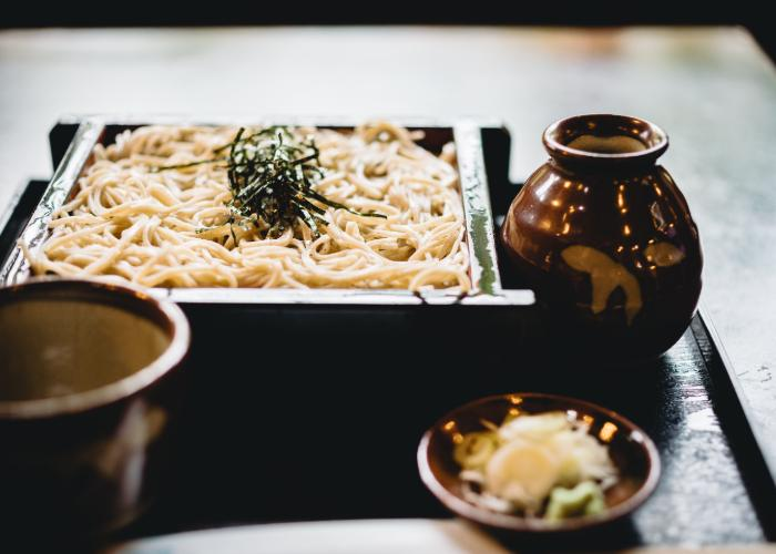 A rectangular tray of soba noodles with thin strips of seaweed.