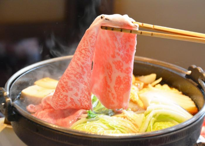A simmering bowl of sukiyaki hotpot with vegetables and a strip of raw beef being placed inside.