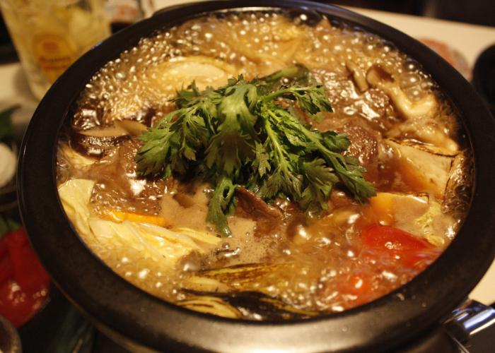 A simmering iron pot of vegetables and meat.