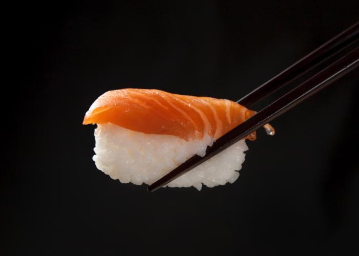 A piece of salmon nigiri sushi on a black backdrop