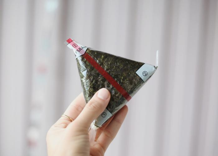 A person holding up a triangular onigiri with plastic wrapping.