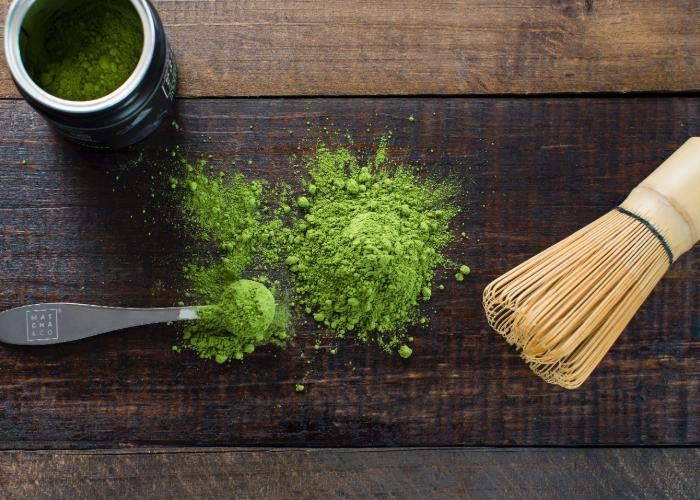 A wooden board with powdered matcha, a scoop, and a traditional tea whisk.