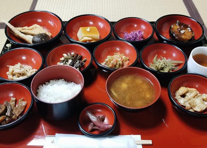 Shojin Ryori, the traditional Japanese vegetarian and Buddhist cuisine. A red tray with a variety of small matching red bowls holding various Japanese vegetarian foods like goma dofu and vegetables
