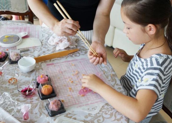 adult helping child make wagashi with chopsticks, colorful flower-shaped wagashi on table