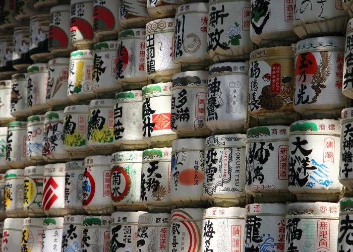 Wall of Japanese sake barrels at shrine or temple