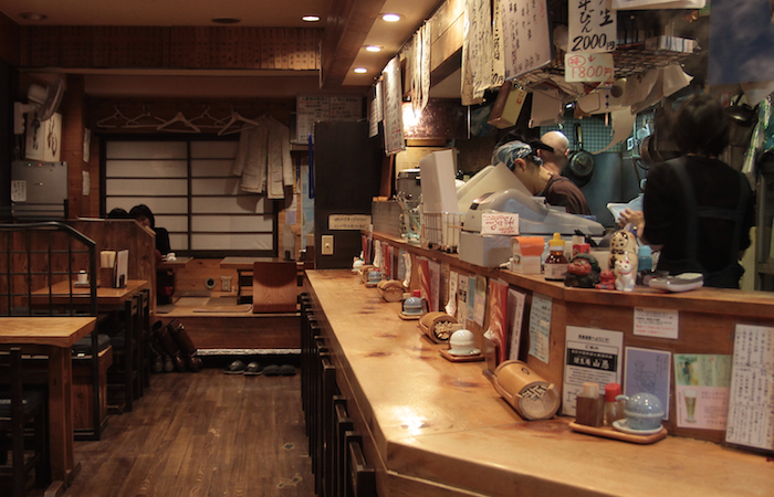 Akaoni 39 Sake Bar in Tokyo with wooden counter, tables, and seated customers