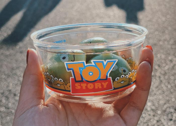Three Toy Story alien mochi is displayed inside a Toy Story themed cup. The cup is being held by a hand model.