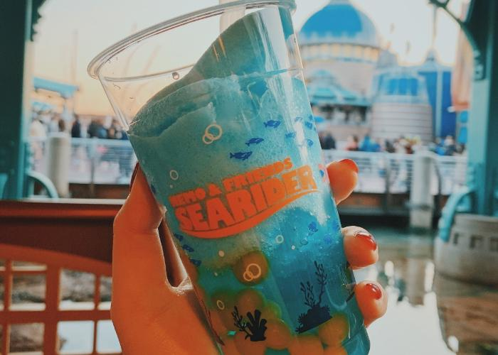 The Deep Sea Pineapple Smoothie has orange boba balls on the bottom. The cup is clear and shows the blue slushy. The cup is decorated with coral and reef sillohetes towards the bottom and a Nemo and Friends Searider logo is on the middle of the cup.