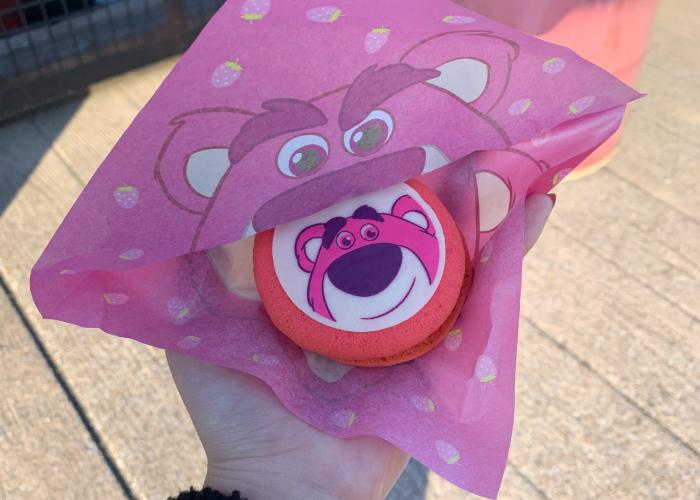 A bright pink cookie sandwich is being held. A picture of Lotso from Toy Story is displayed on top of the cookie. Around the Cookie is a wrapper with Lotso's face.