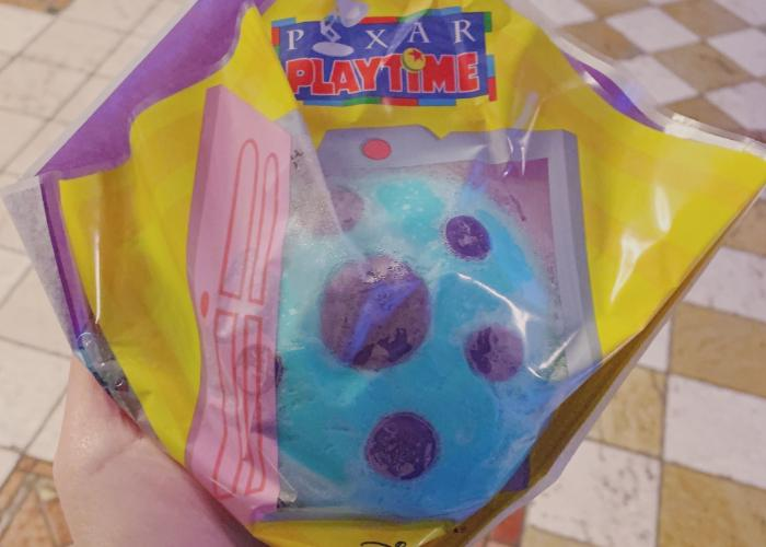 A blue bun with purple polka dots on it is covered with a Pixar playtime themed wrapping. The wrapping is clear in the middle to display the bun.