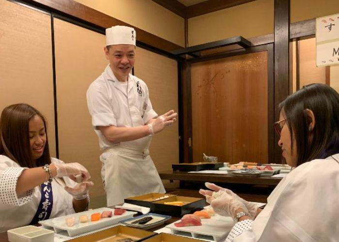 A sushi chef smiles while giving instructions to two women learning to make nigiri.