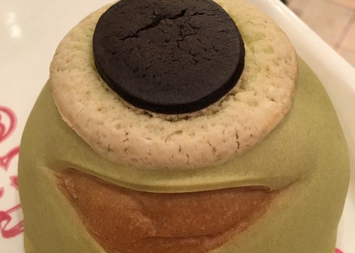 The pictured displayed shows Mike Wazowski Melon Pan up close. The main exterior is green and his smile is a light brown color. On the top is a round, white fluffy circular piece of bread and a chocolate cookie top to form the eye.