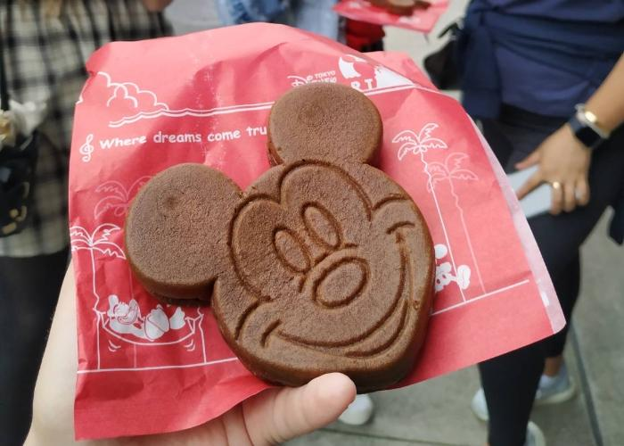 "A brown, Mickey Mouse shape castella is placed on top of red parchment packaging. Mickey Mouse's face is engraved into the castella. On the red packaging towards the top, it says ""where dreams come true""."