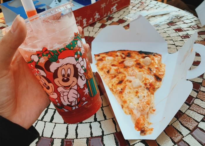 On the left of the picure is Mickey's Sparkling Boba. On the right is the seafood pizza, topped with cheese, scallop, and shrimp. It is placed on a white, triangle shaped paper platter.