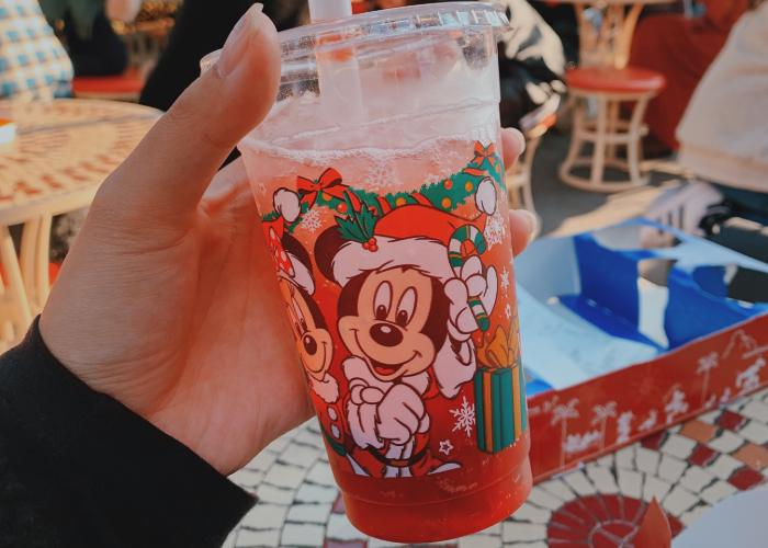 Inside a Mickey Mouse Christmas themed cup is red sparkling drink with boba balls setteled on the bottom. One the cup is Mickey and Minnie Mouse in Santa Claus outfits. There are gift boxes and snowflakes surrounding them.