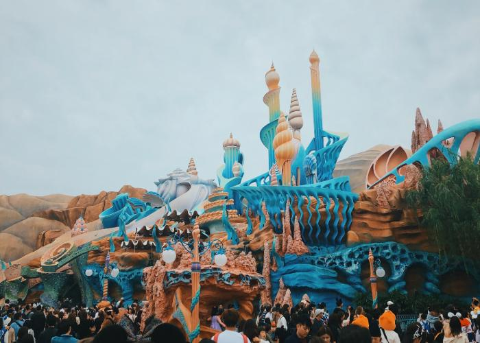 Ariel's castle is consisted of coral shaped structures with flow to represent the ocean. The color scheme is blue, white, and orange. There are people outside waiting to go into the castle.