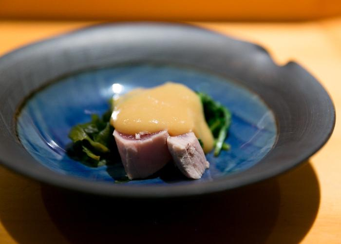 Tuna with seaweed and dollop of yellow Japanese mustard on blue plate