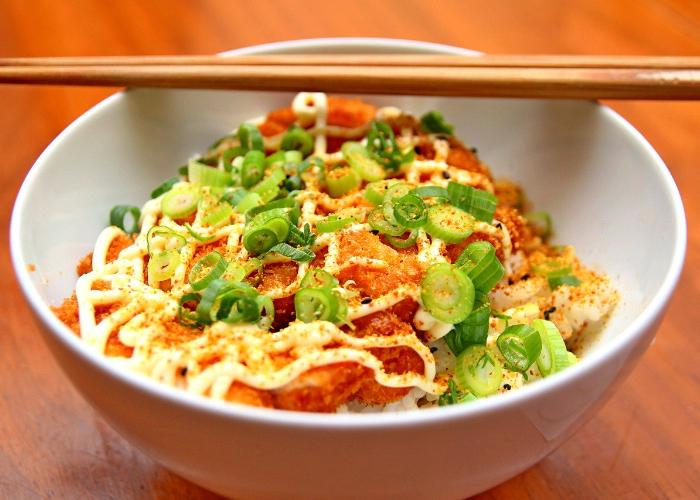 White bowl of breaded meat with seasoning, mayonnaise and green onions, chopsticks on bowl