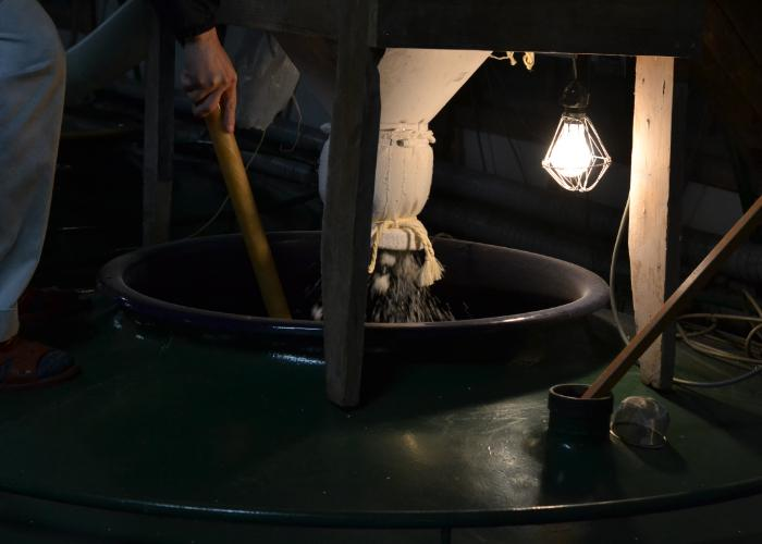 Rice and koji being mixed in a large vat at at a sake brewery