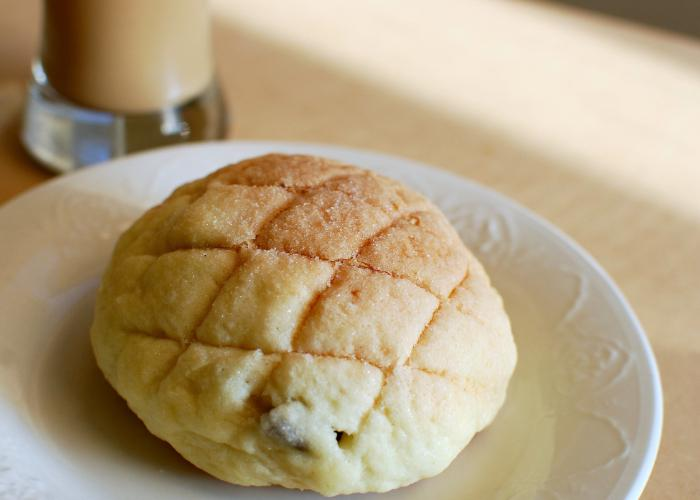 A fresh melon pan bun is placed on top of a white plate. There are checkered shaped grooves on top. In the background, there is a glass of coffee towards the top left side.