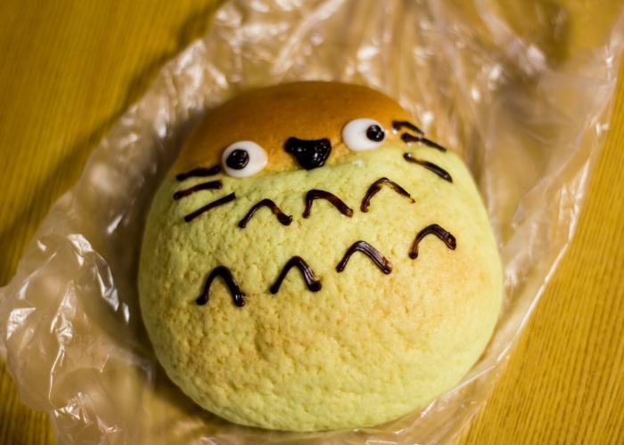 This melon pan looks like Totoro, a famous Ghibli character. There are whiskers and eyes and chocolate drizzle was used to form it.