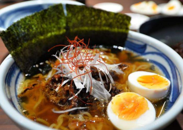 A bowl of ramen packed with noodles, meat, sliced veg, half a boiled egg, and sheets of dried seaweed.