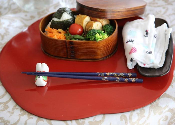A wooden bento box packed with colorful vegetables and rice, with chopsticks resting in front.