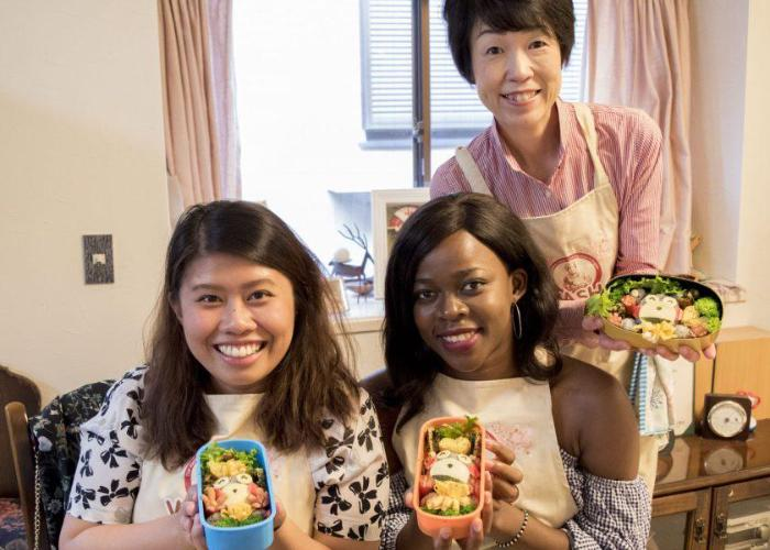 Three women hold up their finished character bento boxes, with
