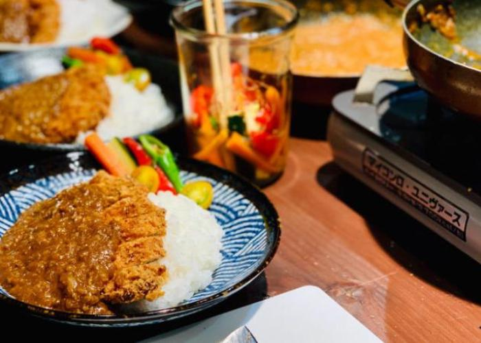 Plates of katsu curry are laid out in a row alongside a hot plate and metal cup of pickled vegetables.