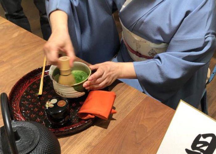 A woman wearing a yukata whisks a bowl of green tea with a bamboo whisk.