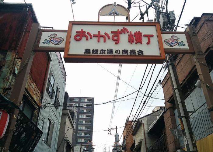 "Okazu Yokocho, a drinking alley in Tokyo during the daytime with a large sign reading ""Okazu Yokocho"" in Japanese"