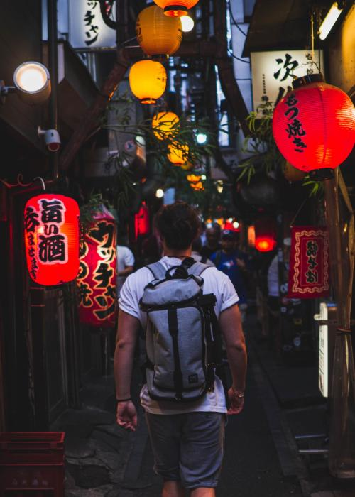 A man wearing a backpack walks through Omoide Yokocho drinking alley in Shinjuku at night with lanterns glowing