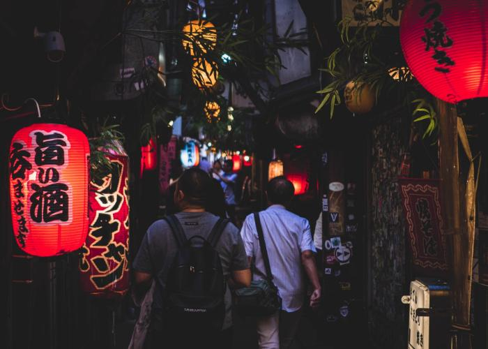 Men walking through a Tokyo Yokocho drinking alley with glowing red lanterns
